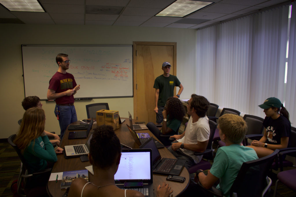 Andrew (standing, left) and Logan (standing, right) lead a meeting of SOAR's current leaders and managers